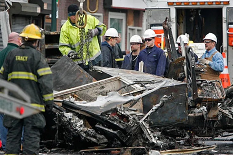 Workers and firefighters watch as the remains of a PGW truck are removed from the site of the Jan. 18, 2011, gas-main explosion in the Tacony section. (Alejandro A. Alvarez / Staff Photographer)