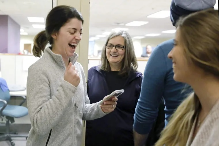 Sarah Bowling reacts after she correctly answered a question while playing HQ Trivia with coworkers Beth Matteson (middle) and Charlotte Gaines (far right) at Artcraft Promotional Concepts in Moorestown on Dec. 29, 2017. Every day at 3 p.m., coworkers huddle in art director Larry Giuffra's office and play HQ Trivia.