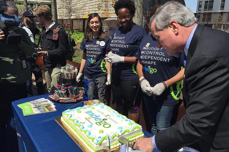 Mayor Kenney takes the first cut of the cake served to attendees at Indego's first birthday celebration on Race Street Pier.