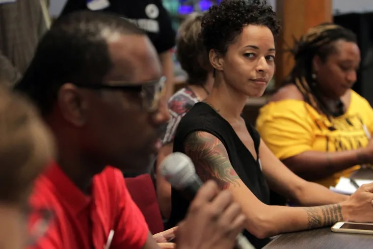 Brianna Jones listens as Asa Khalif, one of the founders of the Philadelphia Coalition for REAL Justice, speaks as local protest leaders hold a meeting to finalize plans for the Democratic National Convention.