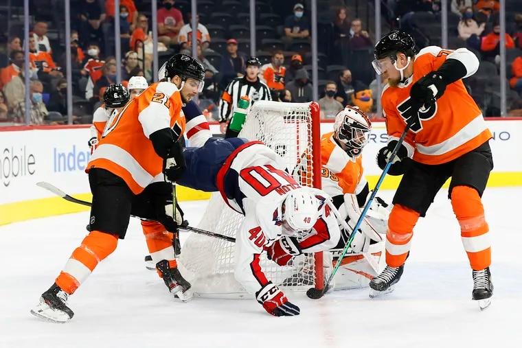 Flyers center Scott Laughton and defenseman Rasmus Ristolainen take down Washington Capitals forward Garrett Pilon during the first period in a preseason game on Saturday, October 2, 2021 in Philadelphia.