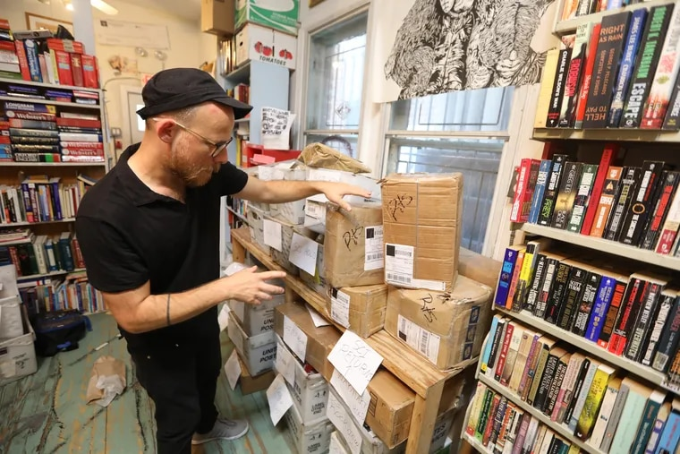 Keir Neuringer and the bins of unmailed packages of books that were supposed to go to PA prison inmates in September. The DOC book ban was lifted Friday.