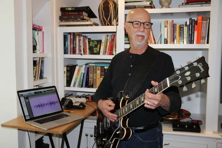 Frank Ingari plays guitar in his home studio.