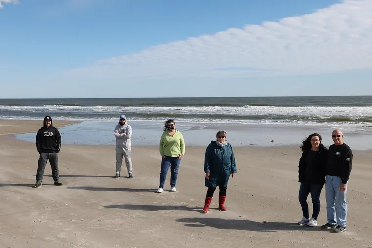 From left, Greg Cudnik, Tony Butch, Suzanne Hornick, Susan Cox, Tricia Conte, and Joe Conte stand on the beach in Ocean City, N.J., on Feb. 6. They are some of the Jersey Shore residents organizing against a planned offshore wind farm, saying it could negatively impact local infrastructure and fishing as well as spoil the view from the beach.