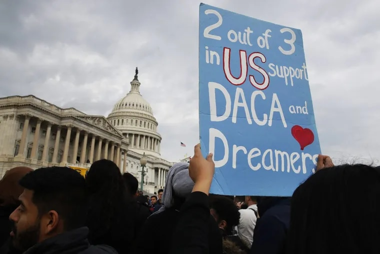 A woman holds up a sign outside the Capitol in support of the Deferred Action for Childhood Arrivals (DACA) program Tuesday on Capitol Hill in Washington.
