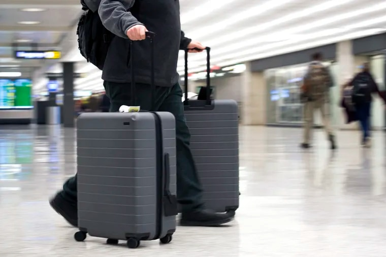 FILE - In this March 26, 2019, file photo, an airline passenger walk in the arrivals terminal at Dulles International Airport in Dulles, Va. Newly documents filed in a federal lawsuit claim that U.S. government searches of phones and laptops at airports are on the rise and are being conducted for reasons beyond immigration and customs enforcement. There were 33,295 searches in fiscal 2018.  (AP Photo/Cliff Owen, File)