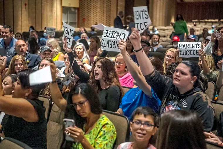 People hold signs and chant during a meeting of the North Allegheny School District school board regarding the district's mask policy Aug. 25. at North Allegheny Senior High School in McCandless, Pa.