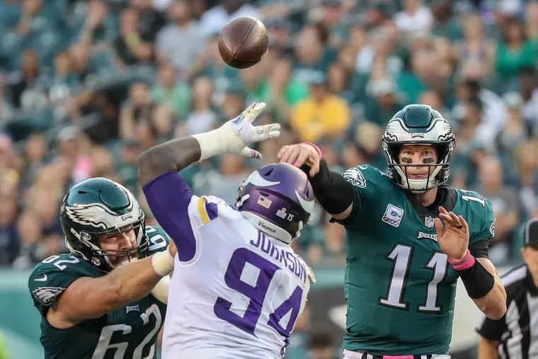 Carson Wentz throws as Jason Kelce tries to keep the Vikings' Jaleel Johnson away during Sunday's loss.