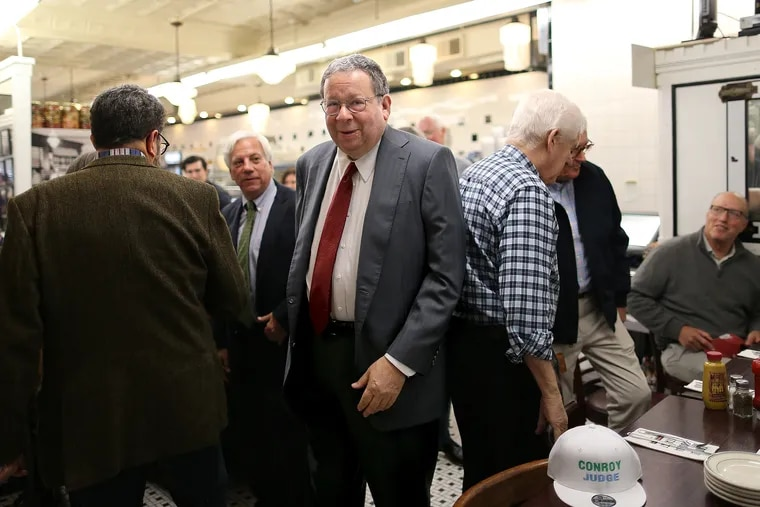David L. Cohen, Senior Executive Vice President & Chief Diversity Officer at Comcast, center, arrives at Famous 4th Street Deli in Philadelphia, PA on November 5, 2019. Local politicians and supporters traditionally gather at the deli on Election Day. Cohen said Thursday he will step away from his operational roles at Comcast.