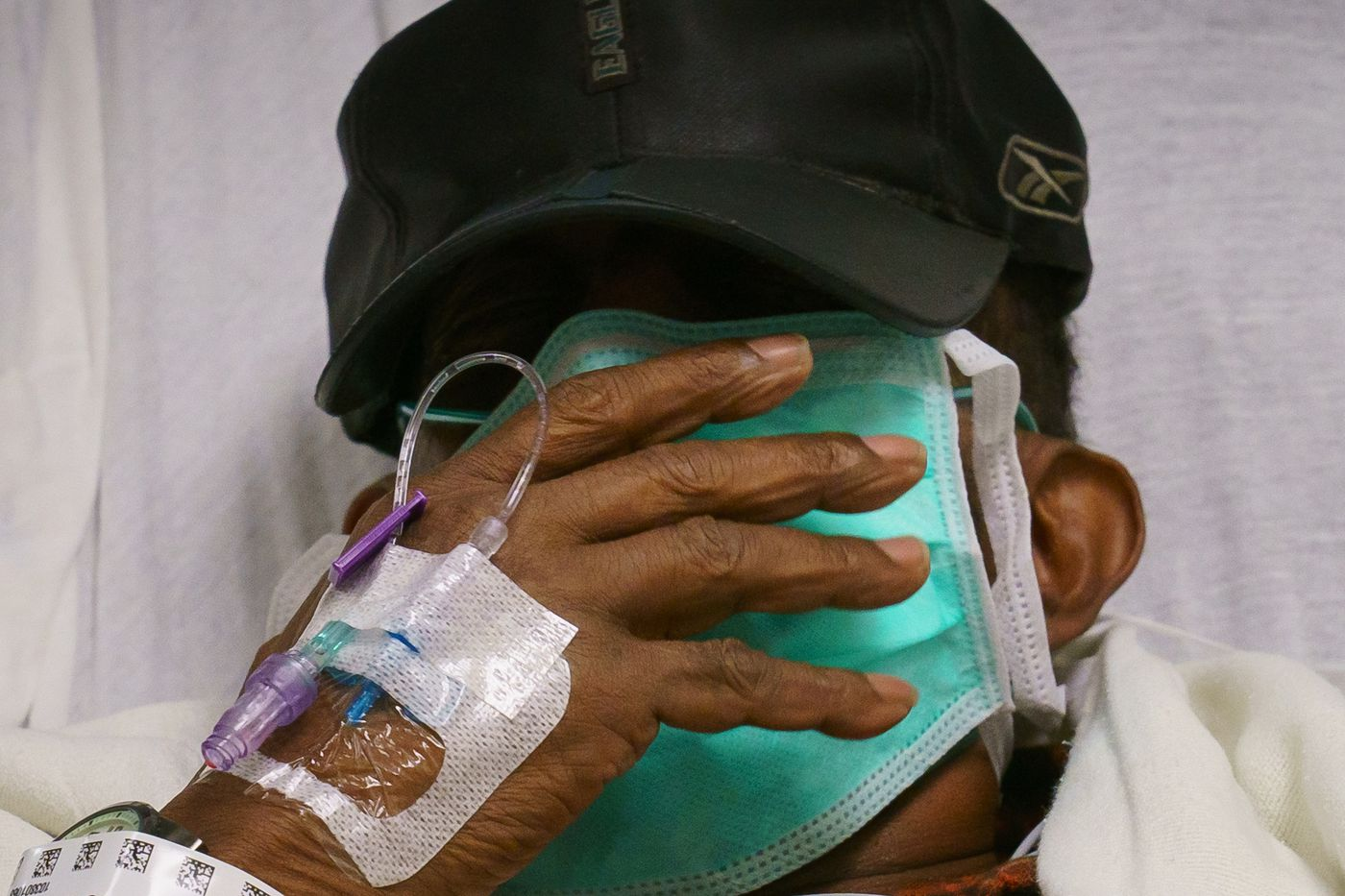 COVID-19 patient Herman Ebo, a 72-year-old retired U.S. Post Office clerk, puts his hand up to his face as he tries to control a bad cough while in the ER last month at Roxborough Memorial Hospital in Philadelphia.