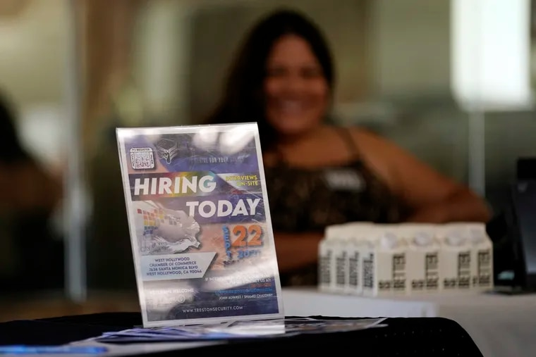 A hiring sign is placed at a booth for prospective employers during a job fair last month in the West Hollywood section of Los Angeles.