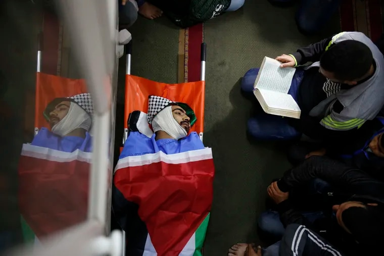 File - In this Tuesday, Dec. 4, 2018 file photo, Palestinians pray by the body of Mohammed Habali 22, during his funeral in the Tulkarem refugee camp near the West Bank city of Tulkarem. The Israeli military says it has opened an investigation into the death of Habali after a video surfaced appearing to show him being shot in the back. The security-camera video shows Habali walking in an alleyway holding a stick when he is shot from behind and falls down on his face. (AP Photo/Majdi Mohammed)