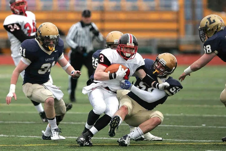 """La Salle's Joe Naji brings down Easton's Zack Bambry as Connor Daly trails the play. Daly registered a team-high 12 tackles, including eight solo stops, in the Explorers' win. """"It's a pretty incredible feeling to be part of this,"""" the senior said."""