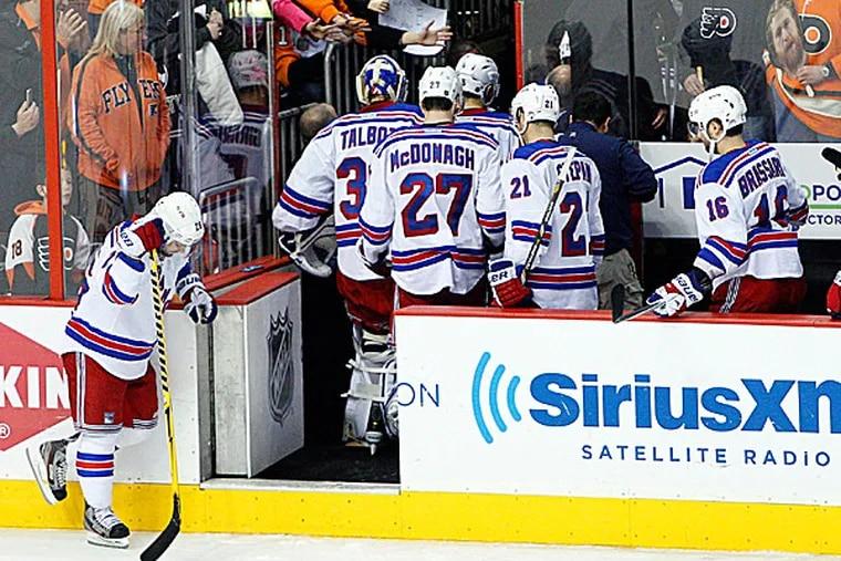 The Rangers' Martin St. Louis hangs his head as his teammates head off the bench to the locker room. (Chris Szagola/AP)