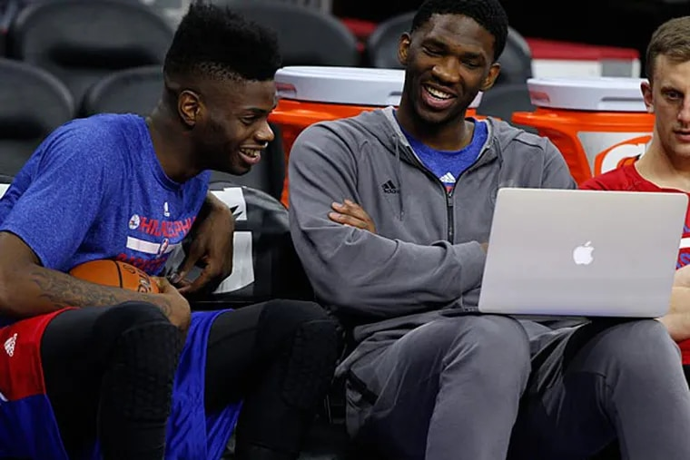 Philadelphia 76ers' Joel Embiid, right, of Cameroon and Nerlens Noel, left, share a laugh while looking at a laptop during warm-ups prior to the first half of an NBA basketball game against the Brooklyn Nets, Wednesday, Nov. 26, 2014, in Philadelphia. (Chris Szagola/AP)