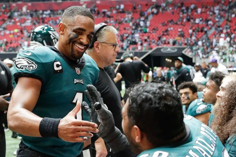 Eagles quarterback Jalen Hurts meets with teammate  offensive tackle Jordan Mailata after the Eagles scored a fourth quarter touchdown against the Atlanta Falcons on Sunday, September 12, 2021 in Atlanta.