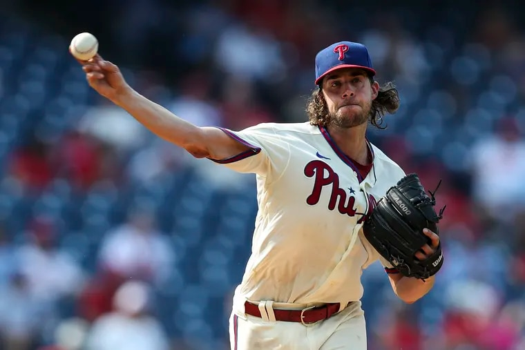 Phillies starting pitcher Aaron Nola throws to first base during the sixth inning against the Colorado Rockies.