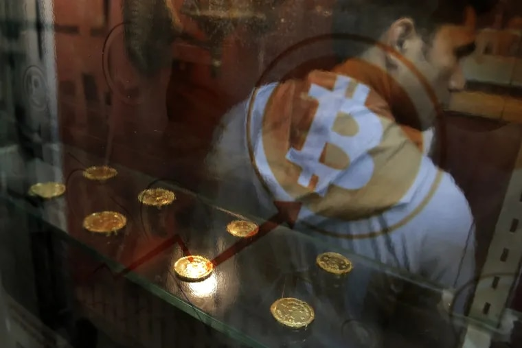 In this Friday, Dec. 8, 2017, file photo, a man uses a Bitcoin ATM in Hong Kong. Bitcoin is the world's most popular virtual currency. Bitcoin and other cryptocurrencies have been plunging.