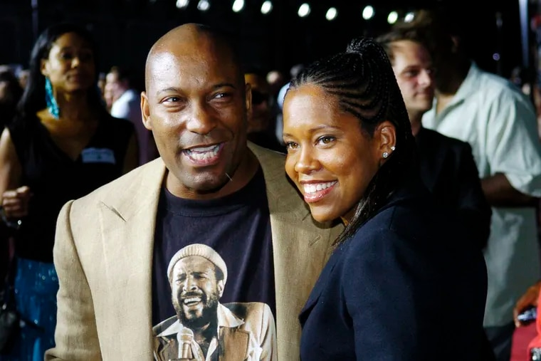 """FILE - This July 20, 2005, file photo shows John Singleton, a producer for the film """"Hustle & Flow,"""" with actress Regina King at the premiere of the film in Los Angeles. Oscar-nominated filmmaker John Singleton has died at 51, according to statement from his family, Monday, April 29, 2019. He died Monday after suffering a stroke almost two weeks ago."""