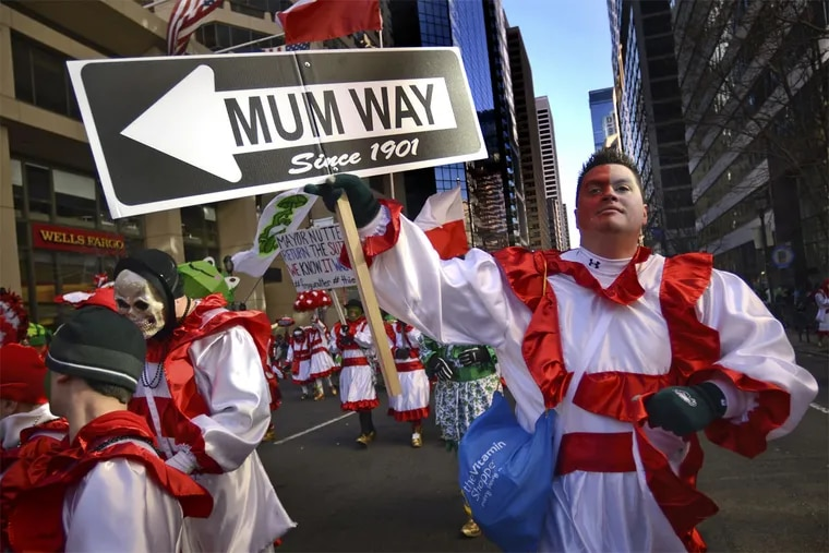 A Froggy Carr wench marches on Market Street with a sign he made to protest the 2015 Mummers Parade's new route - reversing direction and going from City Hall to Washington Avenue.