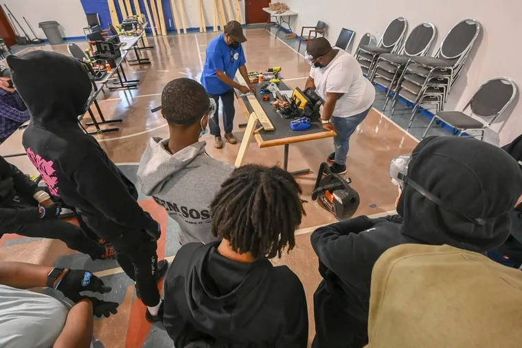 Instructor Greg Palmer (left blue shirt) and Anton Moore, president and founder of Unity in the Community's new Carpentry Academy, work with students as part of a program that teaches young males wood-working and prepares them for a possible career in the industry.