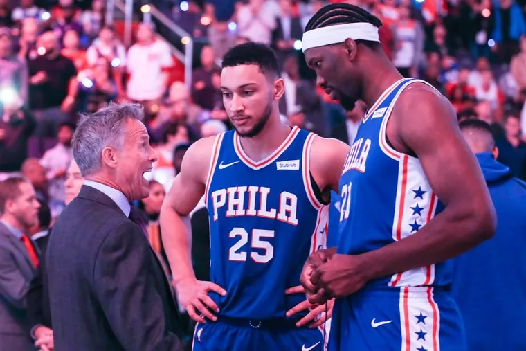 Sixers' coach Brett Brown talks with Ben Simmons and Joel Embiid before their game with the Wizards at the Capital One Arena in Washington, DC, Wednesday, October 18.