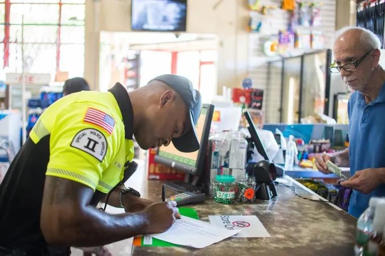 Officer Kerry Dunbar II, 28, signs a police log in a Cedar Food Market on Arctic Avenue in Atlantic City.