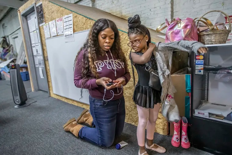 Menda Stewart, left, a nurse and mother of McKenzie Stewart, right, who was diagnosed with type 1 diabetes when she was 4, checks McKenzie's blood sugar levels before allowing her to begin her first of three dance classes on Feb. 1, 2020, at the Eleone Dance Unlimited studios.