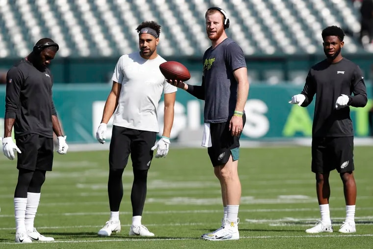 Eagles quarterback Carson Wentz holds the football with wide receivers (from left): Nelson Agholor, J.J. Arcega-Whiteside, and Greg Ward before the  Lions game.
