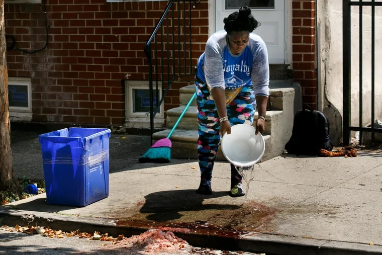 """A woman who prefers to be identified by her nickname """"Tank"""", cleans blood off of the sidewalk on the 2100 block of North 4th Street, Tuesday, July 17, 2018. Multiple people were shot on this block late last night."""