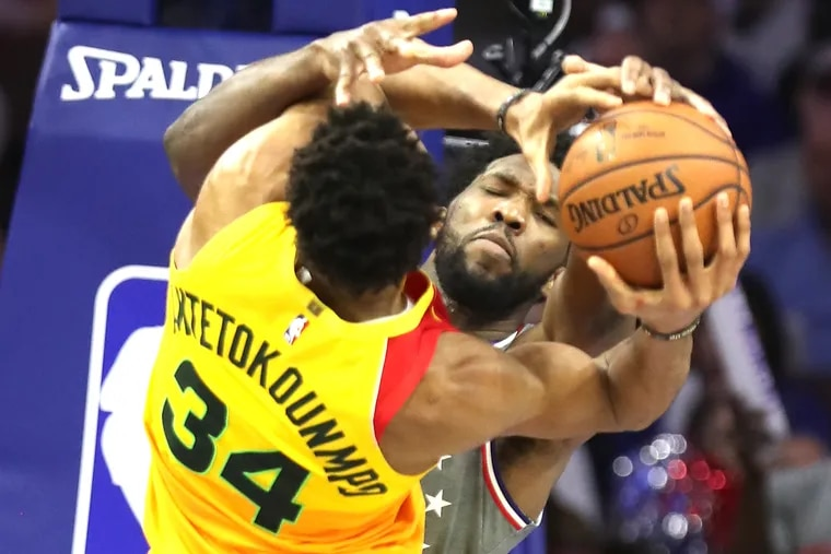Joel Embiid, right, of the Sixers forces a jump ball with Giannis Antetokounmpo, left, of the Bucks at Wells Fargo Center during the 2nd half on April 4, 2019.