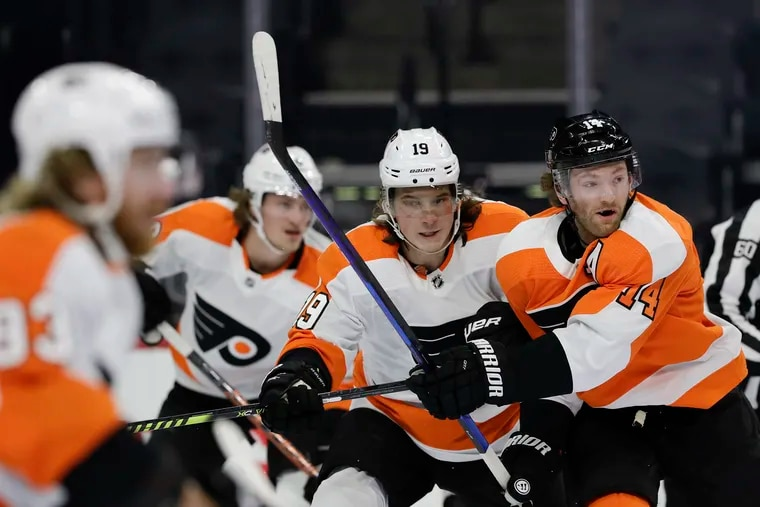 Flyers Team White center Nolan Patrick battles for positioning against Flyers Team Orange center Sean Couturier in the first period during an intrasquad scrimmage Sunday night at the Wells Fargo Center.