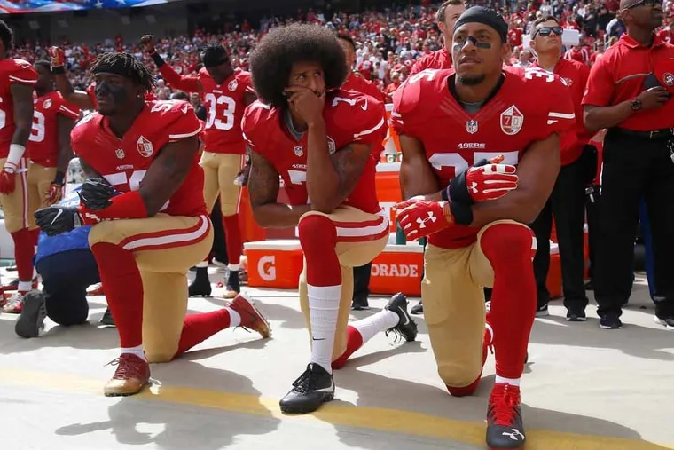 Colin Kaepernick, center, sat, but ultimately decided to kneel for the national anthem last season.