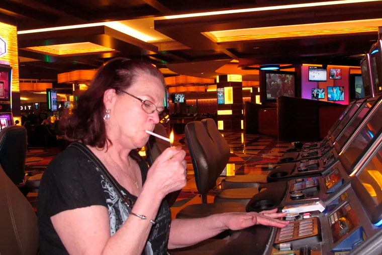 Cheryl Palina of Philadelphia lights a cigarette while playing a slot machine at the Tropicana casino in Atlantic City in March 2016. Smoking was allowed to resume in Atlantic City's nine casinos on July 4, 2021, just over a year after a coronavirus-inspired smoking ban was put in place.