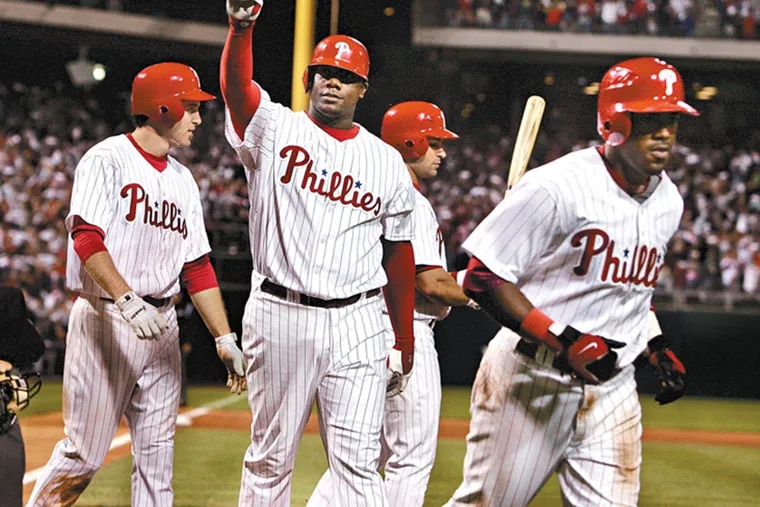 Philadelphia Phillies Ryan Howard (center) acknowledges fans as he celebrates his three-run home run, batting in Jimmy Rollins (right) and Chase Utley (left) during the bottom of the third inning against the Florida Marlins as Citizens Bank Park on September 22, 2006. PHILS23a (Photo by Barbara L. Johnston/Inquirer)