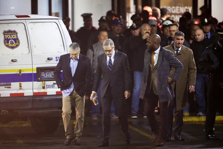 Philadelphia District Attorney Larry Krasner, center, and his Homicide Unit Chief Anthony Voci, left, walk away from the emergency room entrance at Temple University Hospital in North Philadelphia after SWAT Cpl. James O'Connor was fatally shot Friday, March 13, 2020. FOP members and police officers created a human barricade blocking Krasner from entering the hospital.
