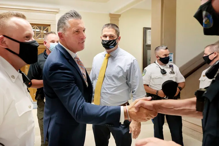 Upper Darby Police Superintendent Timothy Bernhardt (second from left) is greeted by members of law enforcement after being sworn in during a township council meeting in September. Bernhardt says his priority is to adopt a more community-driven approach to policing.