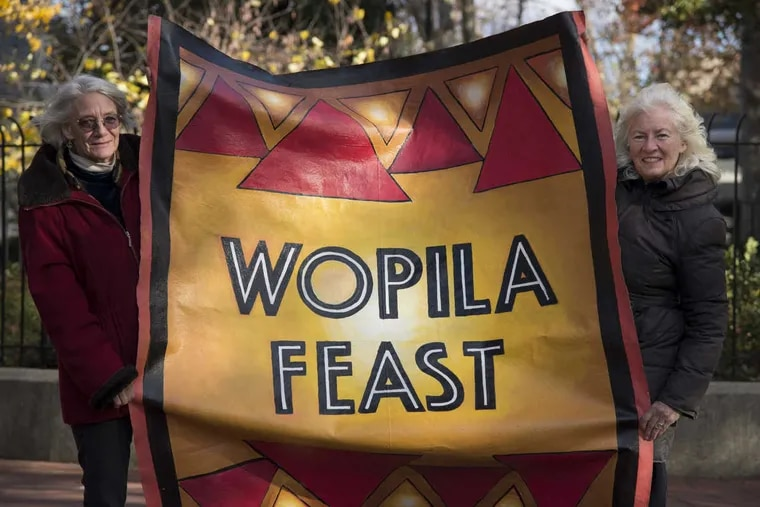 """Artist Lou Ann Merkle (left) and former Philadelphia restaurateur Judy Wicks with Merkle's banner they will be taking to the Standing Rock Sioux Reservation in North Dakota in support of those protesting a pipeline (""""Wopila"""" means """"Thanks"""" in Lakota Sioux). Wicks has arranged donations to feed 2000 people at a Thanksgiving dinner."""