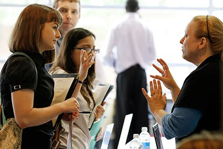 Erica Anselmo, right, from Independence Blue Cross, talks with Ashley Munz, a recent graduate of Franklin and Marshall at the Campus Philly job fair at Temple University last month. (Laurence Kesterson / Staff Photographer)