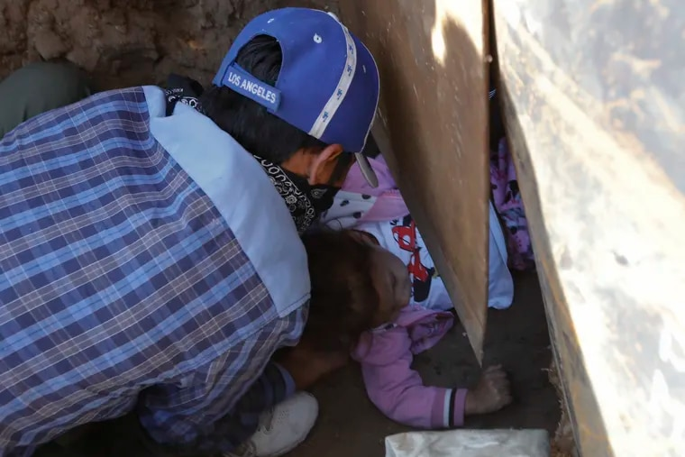 Honduran migrant Charlot Andrea, 3, is passed under the U.S. border wall to her 19-year-old mother Rachel Rivera, who had already crossed, in order to surrender to the U.S. border patrol and request asylum, from Playas de Tijuana, Mexico, Tuesday, Dec. 4, 2018. Weeping as she stayed behind in Tijuana with her Mexican husband, the little girl's grandmother Yesenia said her daughter and granddaughter joined the migrant caravan to flee an abusive husband back in Honduras. (AP Photo/Rebecca Blackwell)
