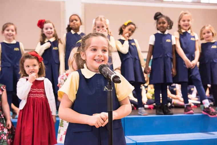 An Agnes Irwin School kindergartener takes the mic during a school event.