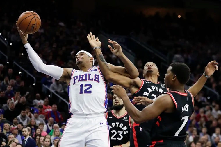 Sixers forward Tobias Harris goes after the basketball against Toronto Raptors guard Fred VanVleet, guard Norman Powell and guard Kyle Lowry.