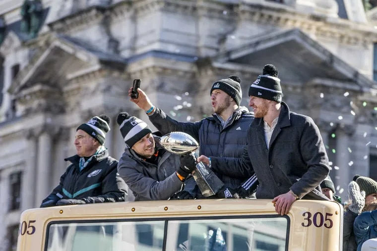 With City Hall in the background Eagle Super Bowl MVP Nick Foles, left,  passes the Vince Lombardi Trophy to Eagle quarterback Carson Wentz, right, to hold up during that part of the parade, while backup quarterback Nate Sudfeld, center, reaches over them both to take a photo of the huge crowd. Eagle owner Jeffrey Lurie, extreme left, takes it all in during the Eagles Super bowl Parade on Thursday February 8, 2018.