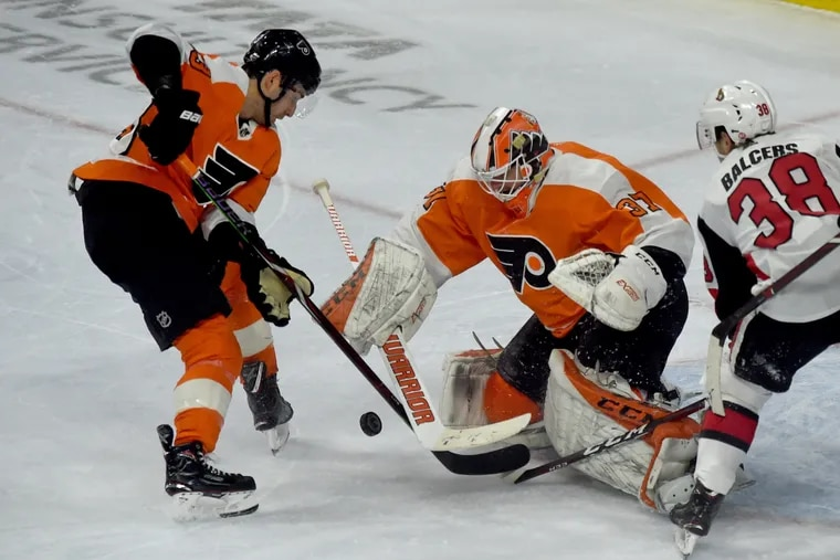 Flyers goaltender Brian Elliott and Shayne Gostisbehere (left) defend the net against Ottawa in a file photo. Elliott will face New Jersey on Tuesday and Gostisbehere could make his season debut.