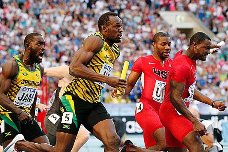 Jamaica's Nickel Ashmeade shouts to Usain Bolt after handing over the baton as United States' Justin Gatlin receives the baton from Rakieem Salaam. (Alexander Zemlianichenko/AP)