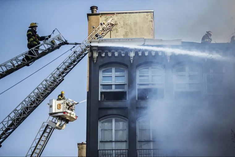 Two ladder trucks pour water onto the building in the 200 block of Chestnut Street where a four-alarm fire broke out in the early morning hours on Sunday.