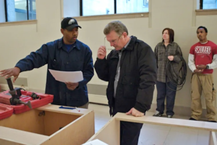 Library electrician Ezekiel Harrell (left) and building superintendent Paul McGeever go over plans before drilling into a wall to prepare the library for a planned cafe.