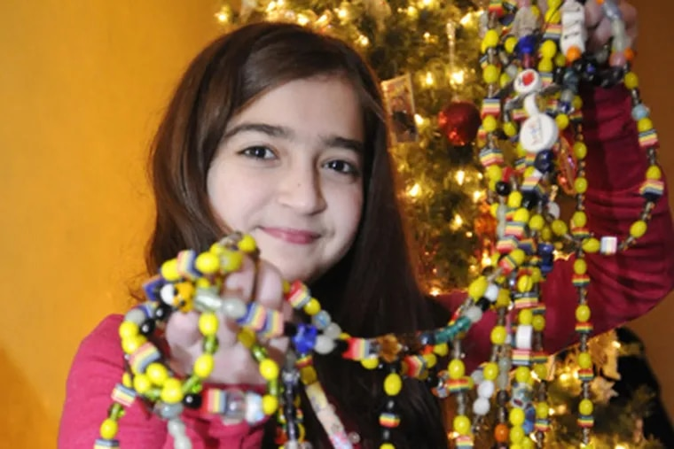 Julia Parmisciano holds her collection of courage beads she received during her stay at Children Hospital of Philadelphia while waiting for a new heart. Each bead represents any procedure done to her during her stay. (Ron Tarver / Staff Photographer)