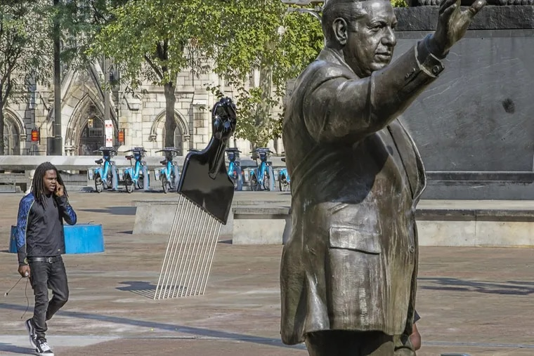 """The statue of Frank Rizzo on Thomas Paine Plaza is joined by a new sculpture called """"All Power to All People"""" , a large Afro Pick with a Black Power salute as the handle was installed Tuesday September 12, 2017. The artist is Hank Willis Thomas of New York. On Tuesday at 1:30 The Mural Arts Project will add its own touch to the Rizzo statue saga with the installation a 12-foot high Afro Pick near the Rizzo statue. The Pop Art object inspired by Claes Oldenburg's Clothespin has a Black Power Fist as its handle. The temporary installation by artist Hank Willis Thomas is the first salvo of Monument Lab a public art project kicking off Wednesday. Tuesday September 12, 2017 MICHAEL BRYANT / Staff Photographer"""