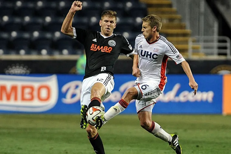 Union forward Aaron Wheeler (12) and New England Revolution midfielder Scott Caldwell (6) battle for the ball during the second half of the U.S. Open Cup match at PPL Park. The Philadelphia Union won the match 2-1.